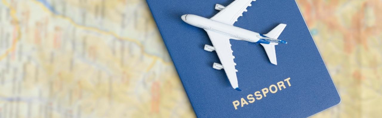 Blue passport and toy aeroplane